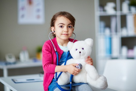 youthful: Little clinician examining her teddybear Stock Photo