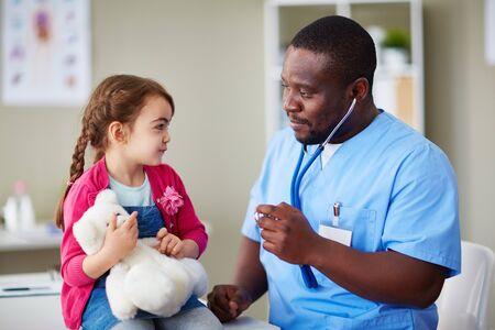 clinician: Cute girl with teddybear looking at clinician at hospital