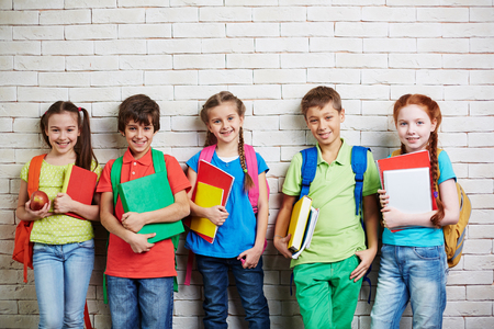 schoolkids: Group of cute schoolkids standing by wall and looking at camera Stock Photo