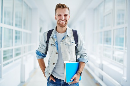 guy portrait: Happy guy with book and touchpad looking at camera