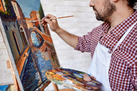 artworks: Modern artist painting landscape with oilpaints