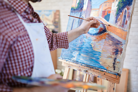 Hand of artist painting Italian landscape