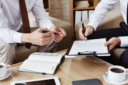 partner: Male employee with pen pointing at contract while showing his partner where to sign it Stock Photo