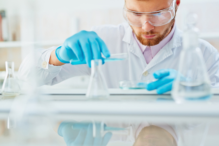 Chemist in protective eyeglasses and gloves working with liquid substances Stock Photo