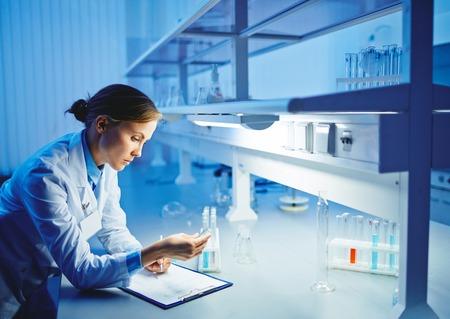Modern chemist studying liquids in laboratory