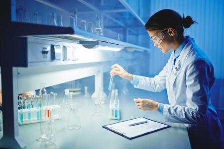 Jonge arts werken met vloeistoffen in laboratorium Stockfoto