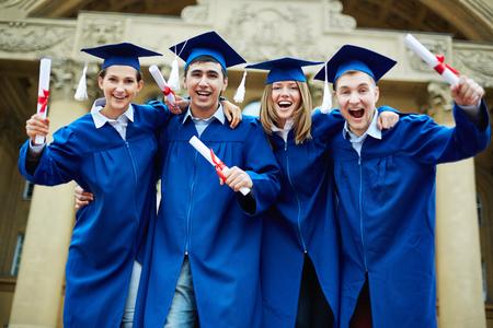 Groupe de diplômés extatiques avec diplômes