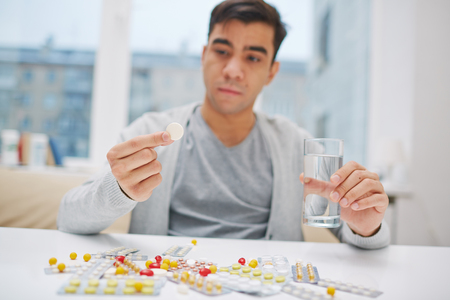 taking pill: Young man sitting at the table and taking a pill