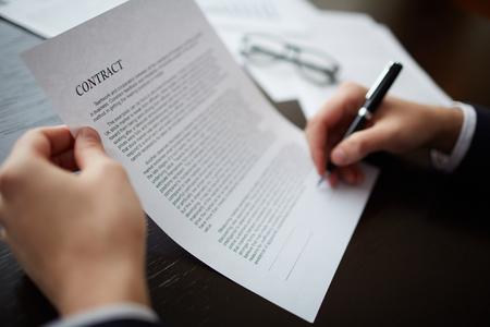 Primer plano de manos de los hombres de firmar un contrato con la pluma Foto de archivo