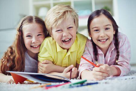 niños riendose: Retrato de los niños alegres que ríen mientras dibuja