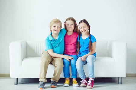boy lady: Group of young friends sitting together on sofa