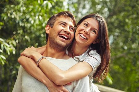 アウトドアの楽しみを持っている若いカップルの肖像画