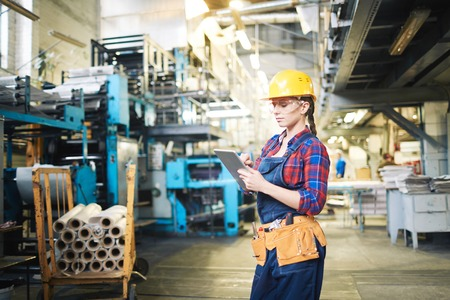 Young engineer in factory checking production