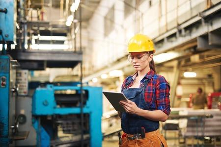 Vrouw in beschermende kleding die touchpad in fabriek