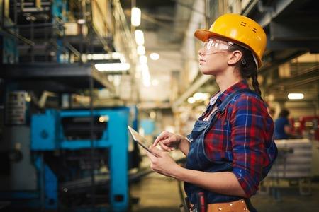 Trabalhador industrial feminino inspetor com touchpad na fábrica