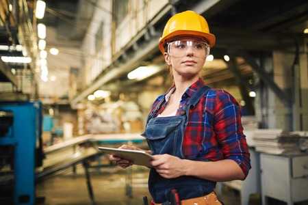 factory: Young factory worker controlling the work Stock Photo