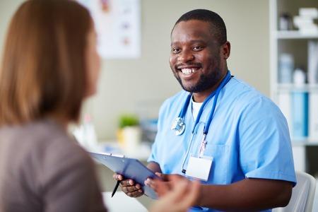 hombres trabajando: Sonriente m�dico africano que trabaja con el paciente en su oficina