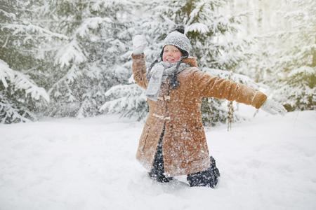 palle di neve: Ragazzo felice in inverno-usura a giocare a palle di neve in inverno parco