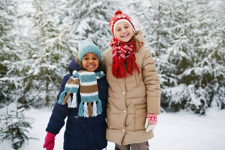 winterwear: Two friendly girls in winter-wear looking at camera in natural environment in winter