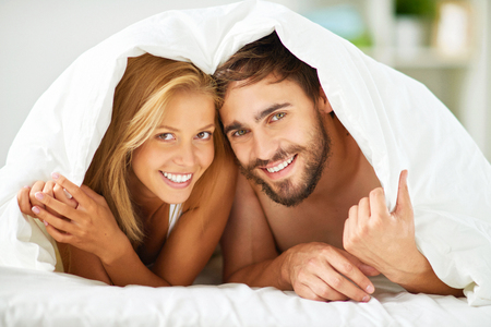 amorous woman: Happy dates under blanket looking at camera with smiles
