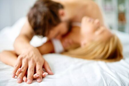 intimacy: Hands of young couple cuddling in bed