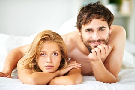 Young couple looking at camera while lying in bed