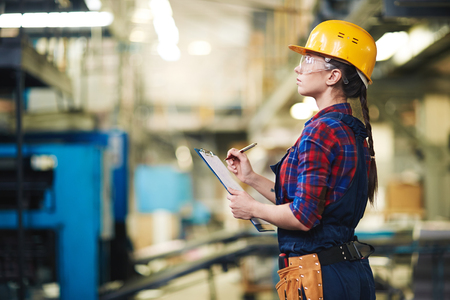 executive helmet: Young female worker in uniform and helmet making notes