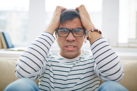 sitting man: Depressed man in glasses sitting at home Stock Photo