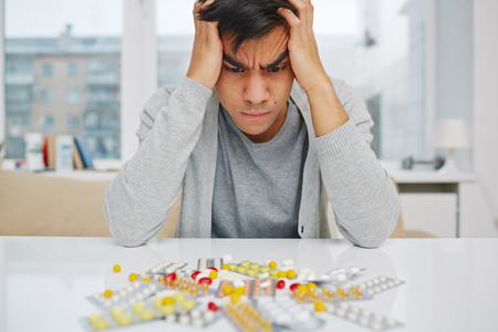 painkiller: Pensive man sitting at the table and looking at medications Stock Photo