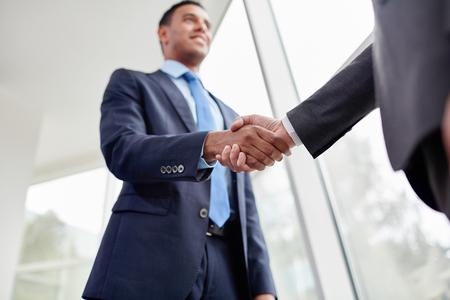 saludo de manos: Los hombres de negocios dándose la mano en la oficina Foto de archivo