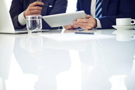 vasos de agua: La gente de negocios utilizando touchpad y discutiendo juntos en la mesa
