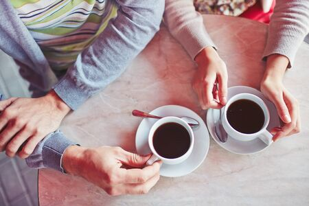 coffee table: Close up of table and hands of young couple enjoying a cup of coffee at sidewalk restaurant Stock Photo