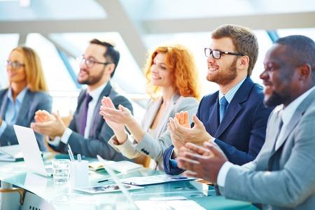 Les gens d'affaires applaudissent lors de la conférence