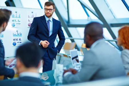 negócio: Homem de negócios novo que faz a apresentação a seus colegas