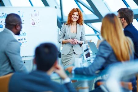 gente adulta: Sonriente mujer de negocios que presenta proyecto de negocio a sus socios