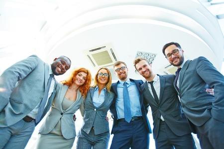 Equipo de negocios sonriente de pie juntos en una fila y abrazando Foto de archivo