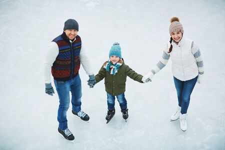 two parents: Two parents with son skate in ice skating in winter Stock Photo