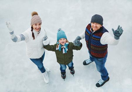Retrato de familia de tres personas en la pista de patinaje