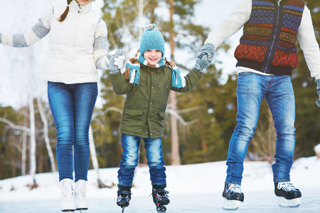 iceskating: Happy little boy ice-skating with his parents together Stock Photo