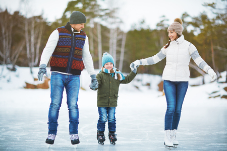아이의 손과 스케이트를 타고 스케이트를 타는 젊은 가족
