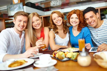 almuerzo: Retrato de amigos felices que almuerzan junto en el café