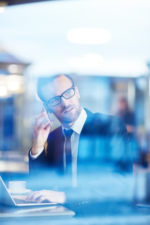 corporate consulting: Confident businessman speaking on the phone and networking in cafe