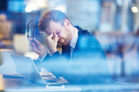 Młoda zmęczony biznesmen siedzi z głową na laptopa