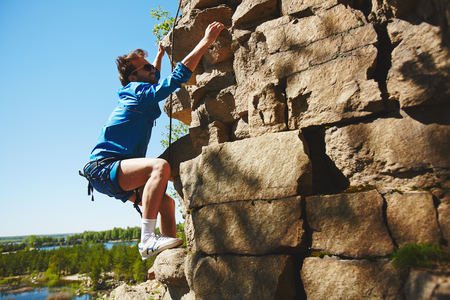 rock climbing: Active young sportsman climbing on cliff