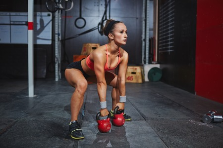 gym workout: Strong and active woman lifting heavy barbells in gym Stock Photo