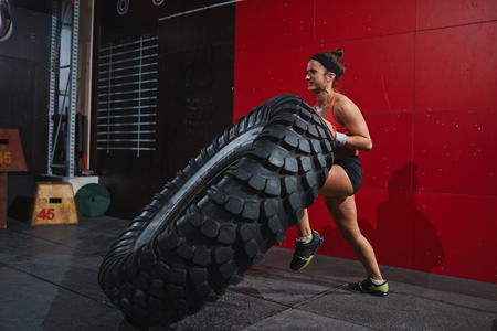flipping: Strong female in sportswear flipping tyre