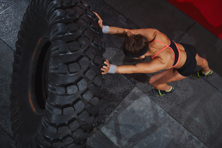 Strong sporty woman flipping tyre Stok Fotoğraf