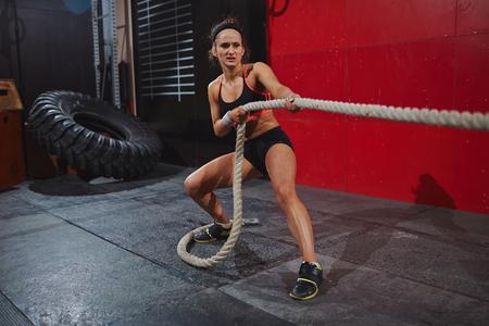 Actieve jonge vrouw trekt touw in de gymzaal