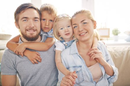 beautiful boy: Happy family of young parents and their two children at home Stock Photo