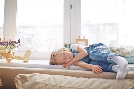 petite fille triste: Sad petite fille en denim couché ensemble sur rebord de la fenêtre